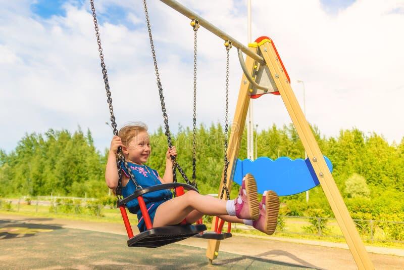 Den lyckliga flickan f?r det lilla barnet som skrattar och sv?nger p? en gunga i staden, parkerar i sommar royaltyfri foto