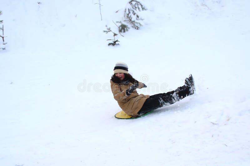 Den lyckliga flickan går ner på en släde, bakfram royaltyfria bilder