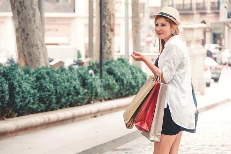 Den lyckliga flickan går till och med gatan, når han har shoppat Henne som rymmer royaltyfri bild