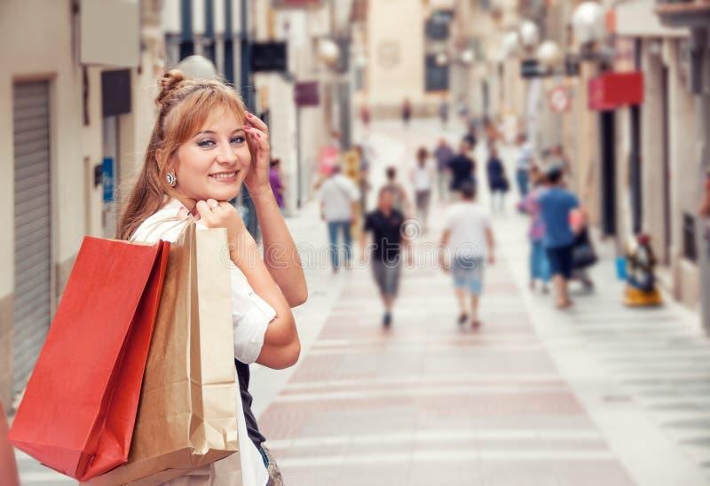 Den lyckliga flickan går till och med gatan, når han har shoppat Henne som rymmer royaltyfria foton