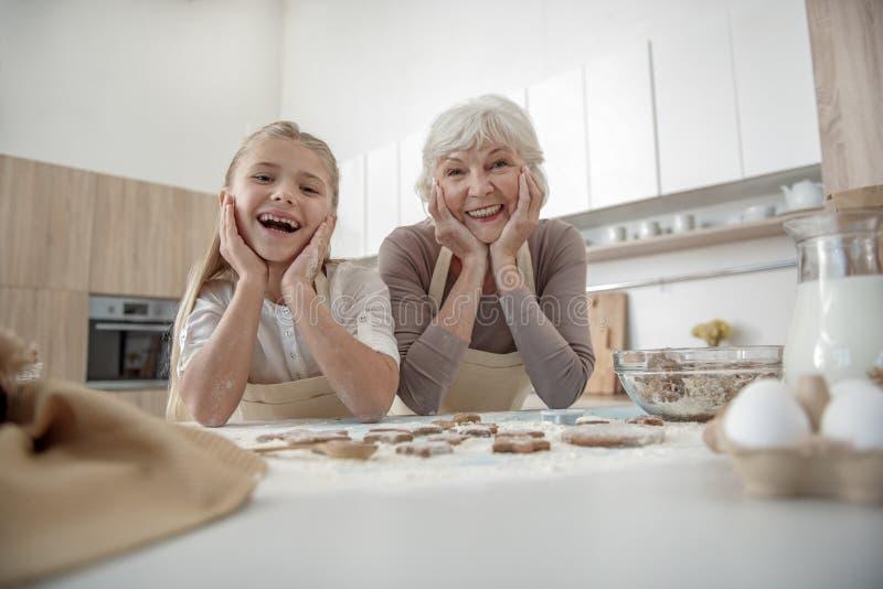 Den lyckliga flickan gillar för att laga mat med hennes farmor royaltyfri bild