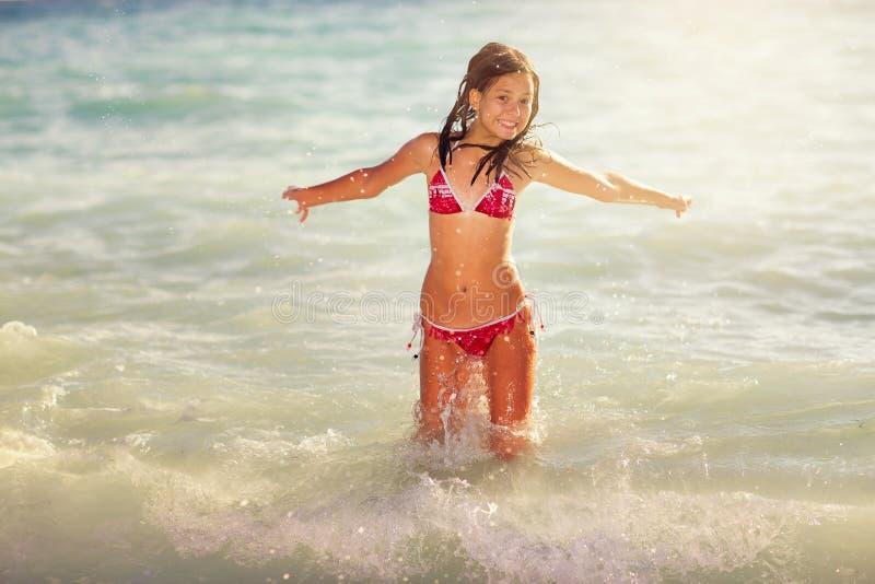 Den lyckliga flickan hoppar på havsvågorna fotografering för bildbyråer