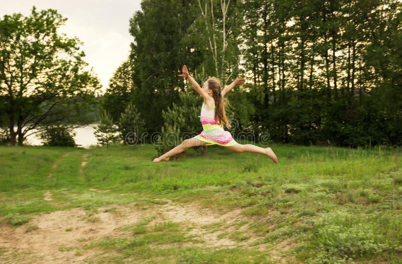 Den lyckliga flickan hoppar till himlen i den gula ängen på solnedgången royaltyfri bild