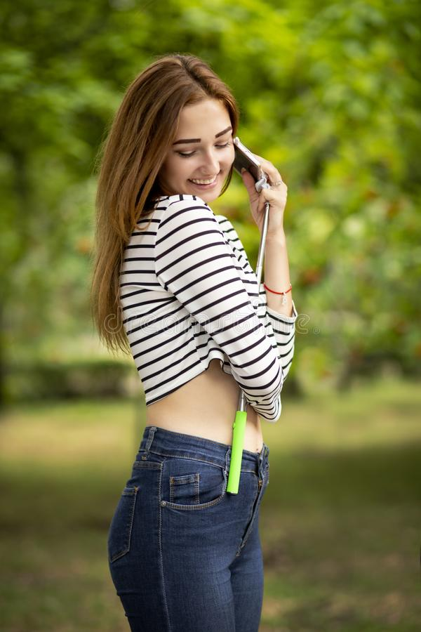 Den lyckliga flickan i en sommarstad parkerar att omfamna smartphonen på selfiepinnen, begreppstonåringlivsstil och den elektroni arkivfoton