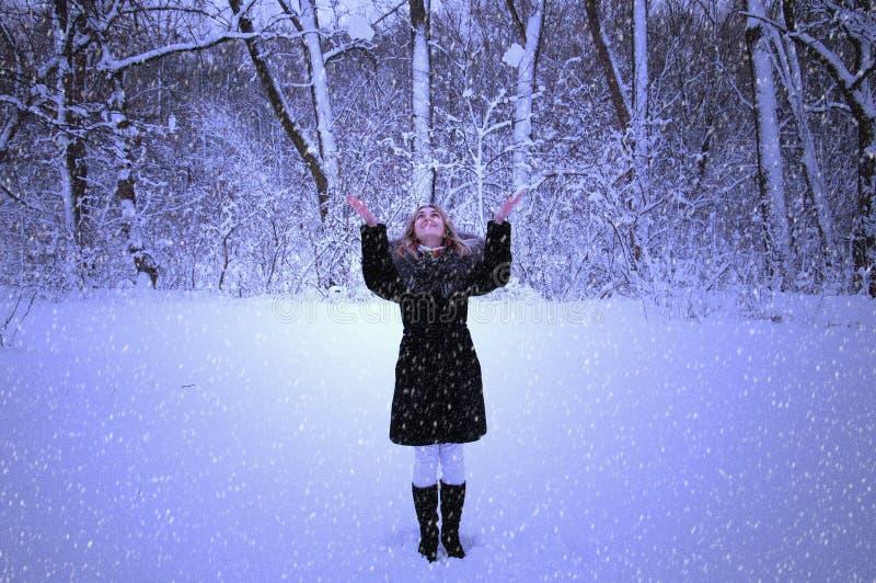 Den lyckliga flickan i ett snöfall går i aftonen parkerar, jublar, ler royaltyfri bild