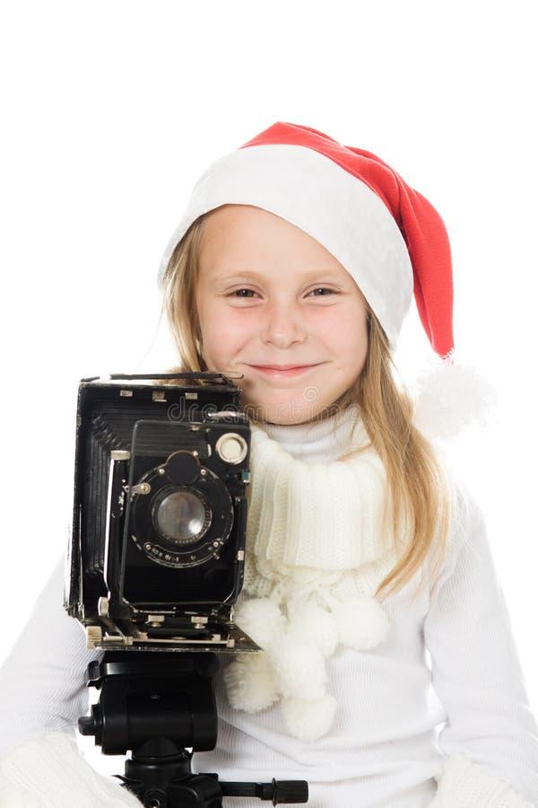 Den lyckliga flickan i jul kostymerar med den gammala kameran arkivfoto