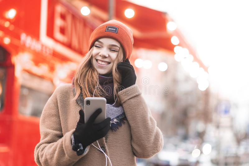Den lyckliga flickan i lag går på gatan, lyssnar till musik i hörlurar med hennes stängda ögon och rymmer smartphonen i händer nä royaltyfri fotografi