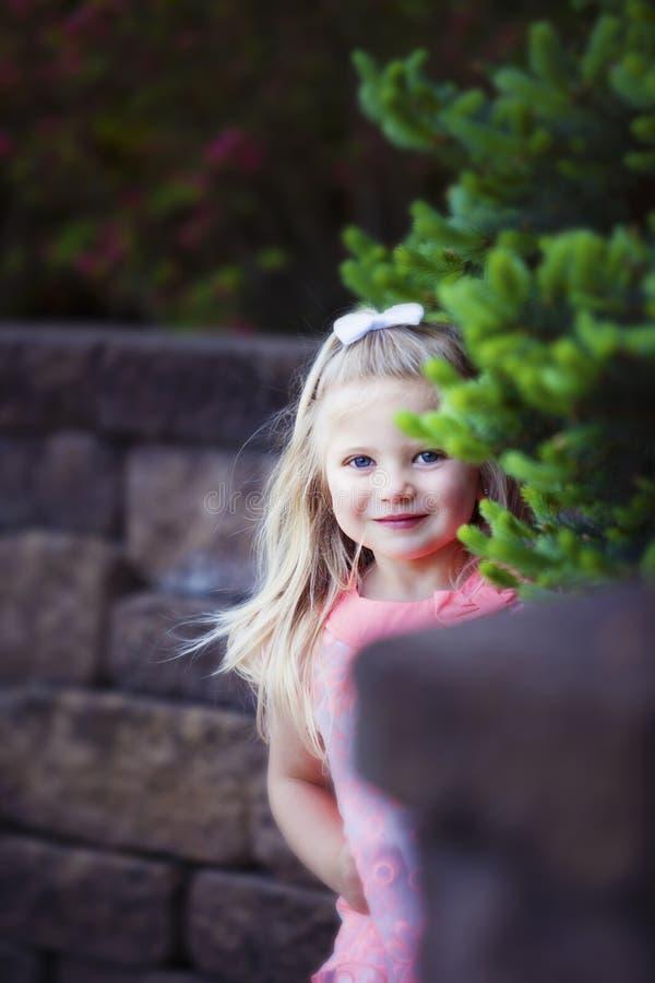Den lyckliga flickan kikar omkring arkivbilder