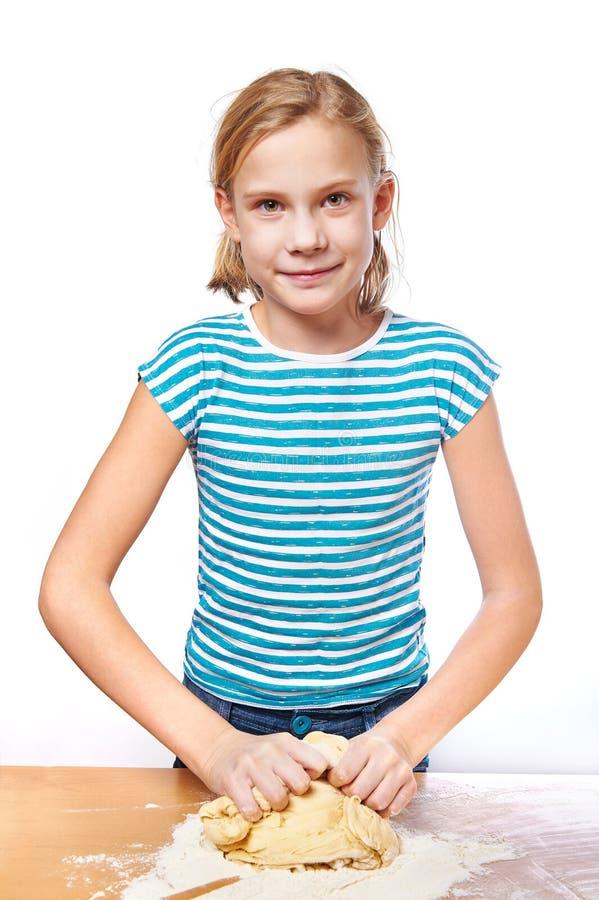 Den lyckliga flickan knådar deg för paj på det isolerade köksbordet fotografering för bildbyråer