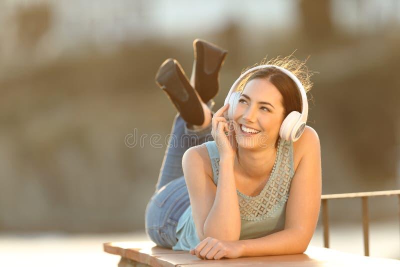 Den lyckliga flickan lyssnar till musik som ser sidan royaltyfri foto