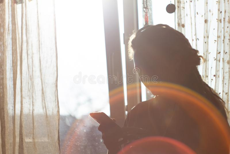 Den lyckliga flickan på ett fönster i strålar av en resningsol arkivbild