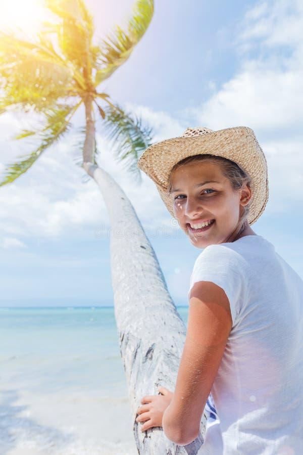 Den lyckliga flickan sitter på en palmträd i en tropisk strand royaltyfria bilder