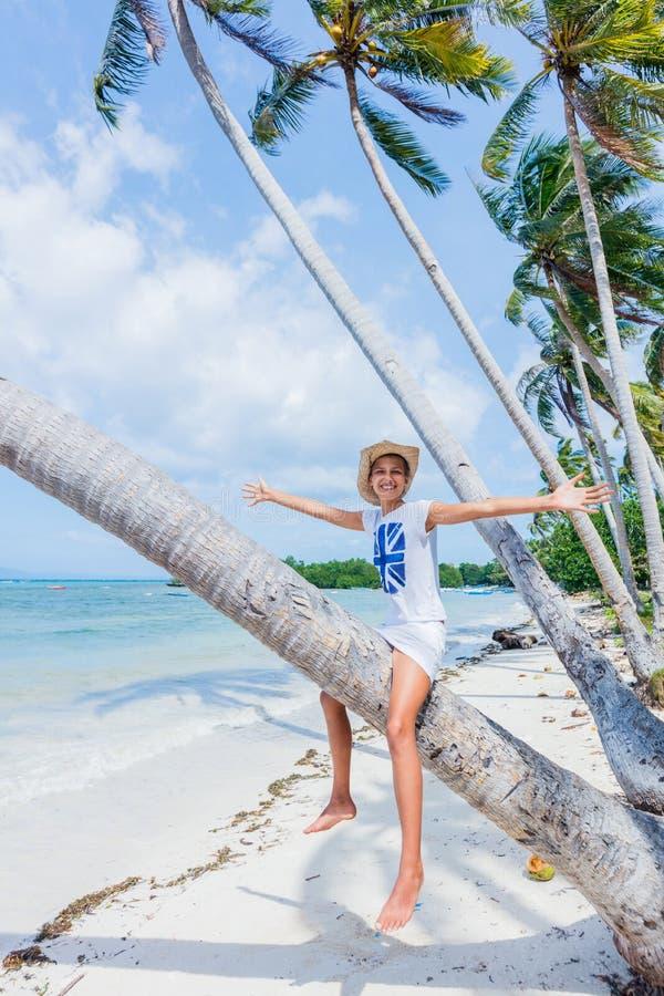 Den lyckliga flickan sitter på en palmträd i en tropisk strand arkivbild