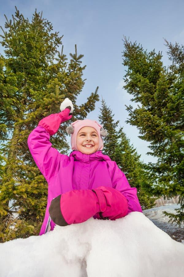 Den lyckliga flickan som är klar att kasta, kastar snöboll under leken royaltyfri fotografi