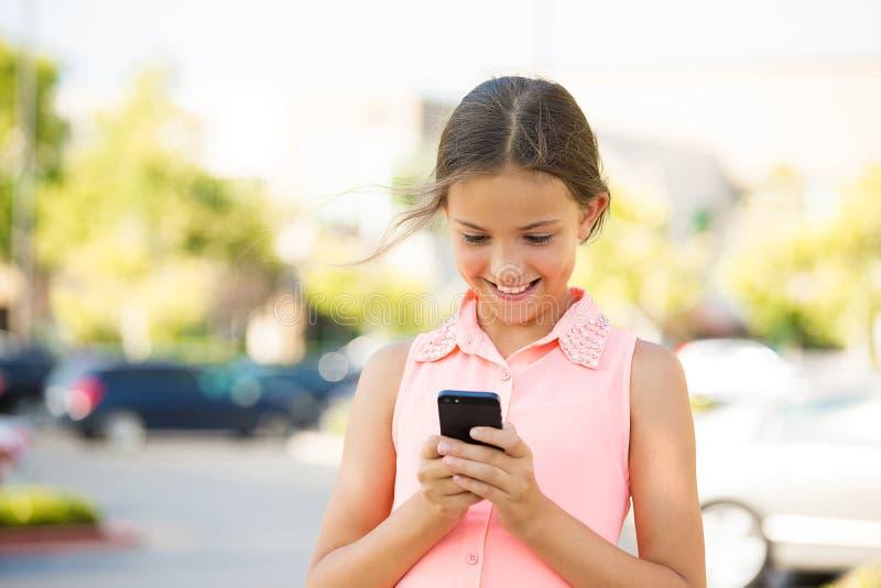 Den lyckliga flickan som kontrollerar hennes nytt, ilar telefonen arkivfoton