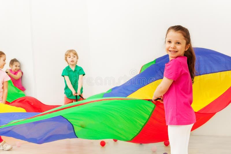 Den lyckliga flickan som spelar med färgrikt, hoppa fallskärm i idrottshall arkivbild