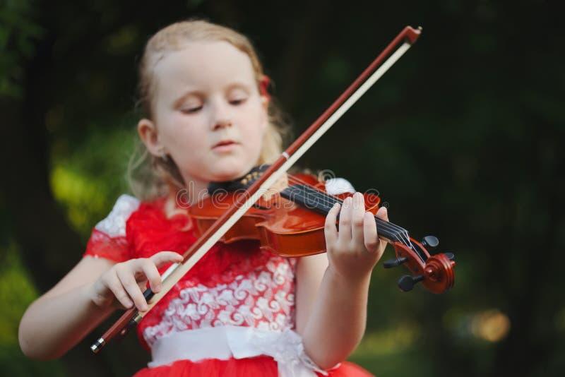 Den lyckliga flickan spelar fiolen i sommar parkerar royaltyfria bilder