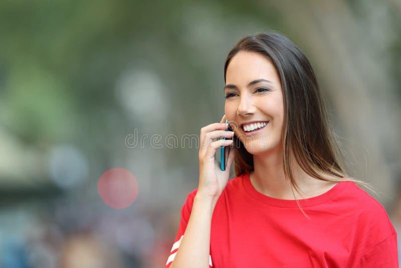 Den lyckliga flickan talar på telefonen och går på gatan royaltyfria bilder