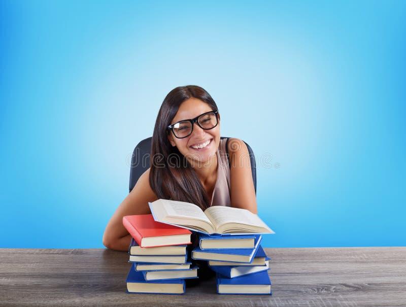 Den lyckliga flickastudenten avslutar hennes studie royaltyfria bilder