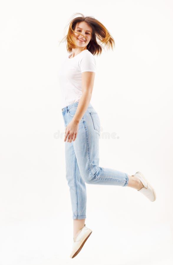 Den lyckliga flickatonåringen i t-skjorta och jeans hoppar arkivbilder