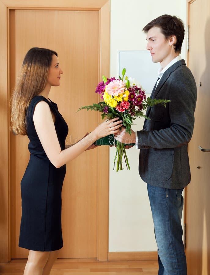 Den lyckliga frun tar gruppen av blommor från hennes make royaltyfri fotografi