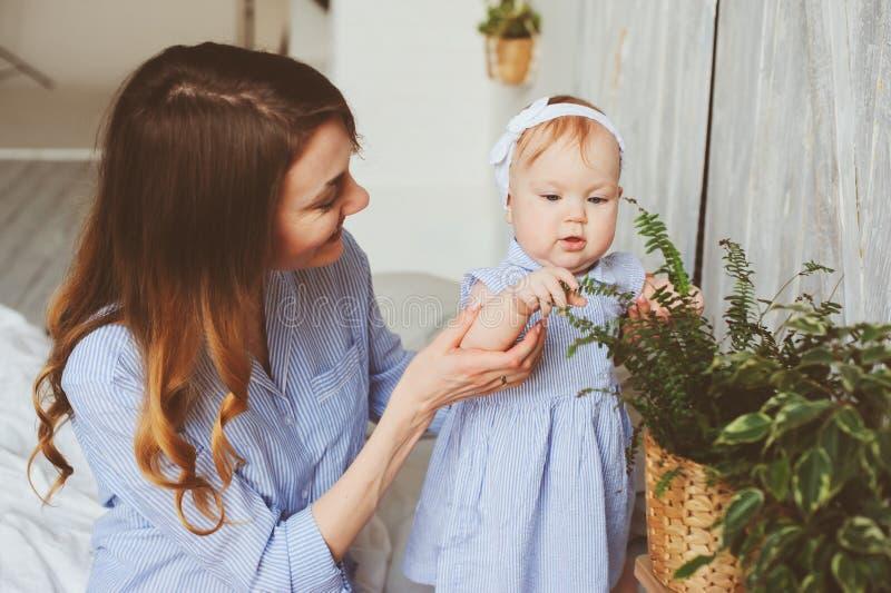 Den lyckliga den gamla modern och 9 månaden behandla som ett barn, i att matcha pyjamas som spelar i sovrum i morgonen royaltyfria bilder