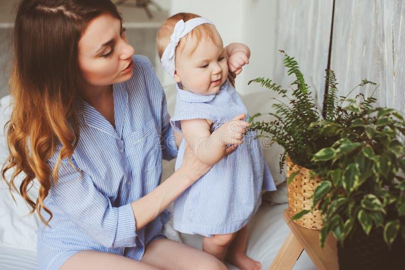 Den lyckliga den gamla modern och 9 månaden behandla som ett barn, i att matcha pyjamas som spelar i sovrum i morgonen arkivbilder