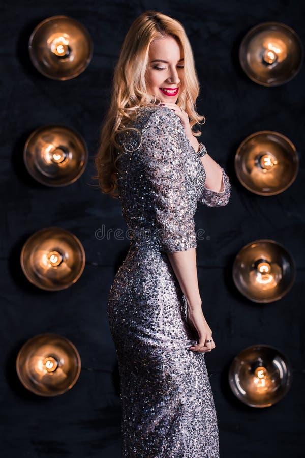 Den lyckliga glade blonda kvinnan i ett långt försilvrar klänningen på en svart bakgrund Beröm parti, nytt år royaltyfri bild