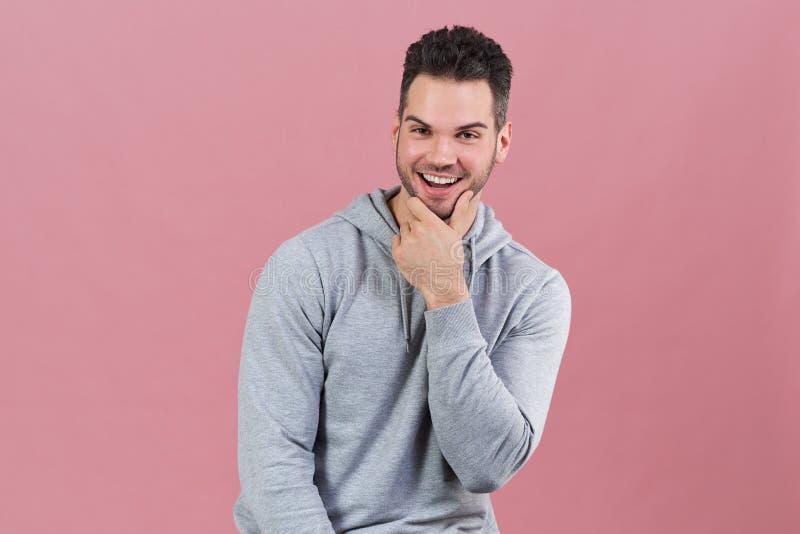 Den lyckliga glade mannen med skägget i grå hoodie skrattar och sätter hans hand till hakan Positiva sinnesrörelser och ett säker arkivbild