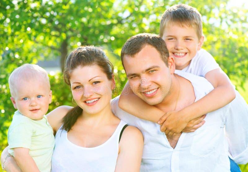 Den lyckliga glade unga familjen i sommar parkerar royaltyfria foton