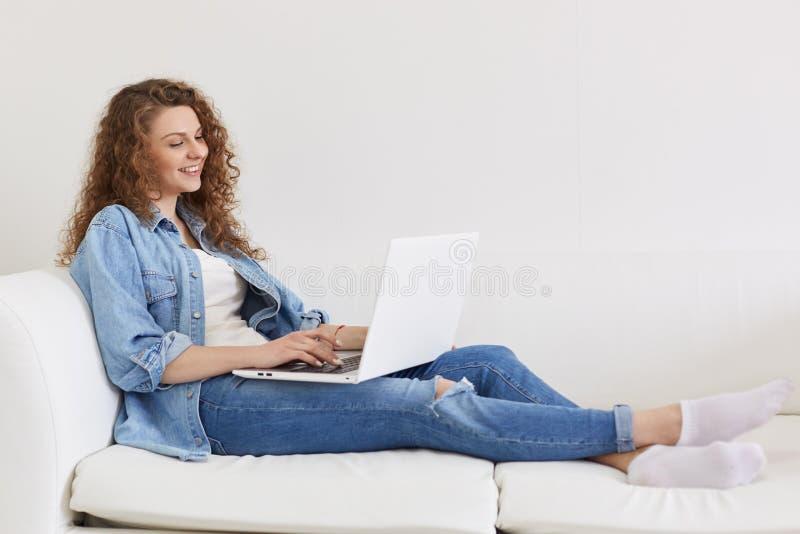 Den lyckliga gladlynta unga kvinnlign som ligger på hennes vita soffa och att ha vilar och att rymma bärbara datorn på hennes ben royaltyfri bild