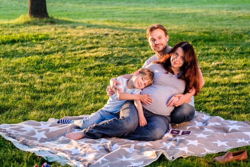 Den lyckliga gravida familjen av att förvänta som tre är nytt, behandla som ett barn royaltyfri fotografi