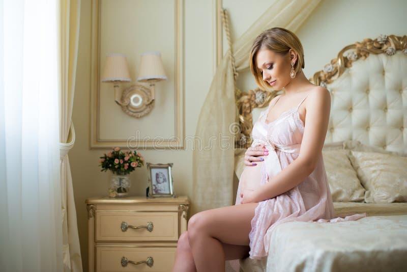 Den lyckliga gravida flickan sitter i inre med lyxigt italienskt möblemang och kramar magen royaltyfria foton