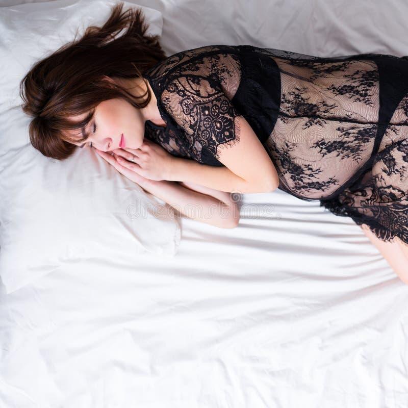 Den lyckliga gravida kvinnan i svart snör åt damunderkläder som sover i säng royaltyfria bilder