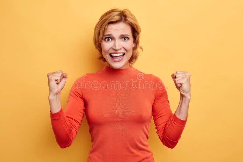 Den lyckliga gulliga charmiga unga kvinnan firar prestationmål arkivbilder