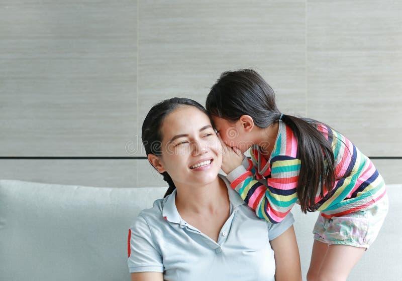 Den lyckliga gulliga lilla asiatiska barnflickan som viskar en hemlighet till hennes unga mödrar, gå i ax hemma Familj och förhål arkivbild