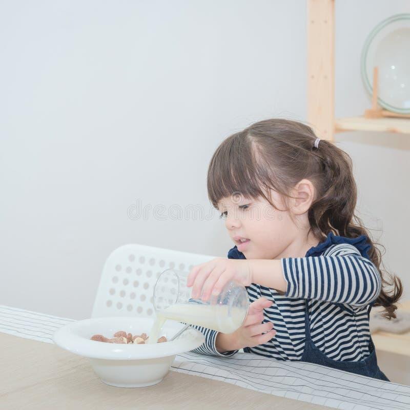 Den lyckliga gulliga lilla flickan förbereder den sunda frukosten royaltyfria bilder