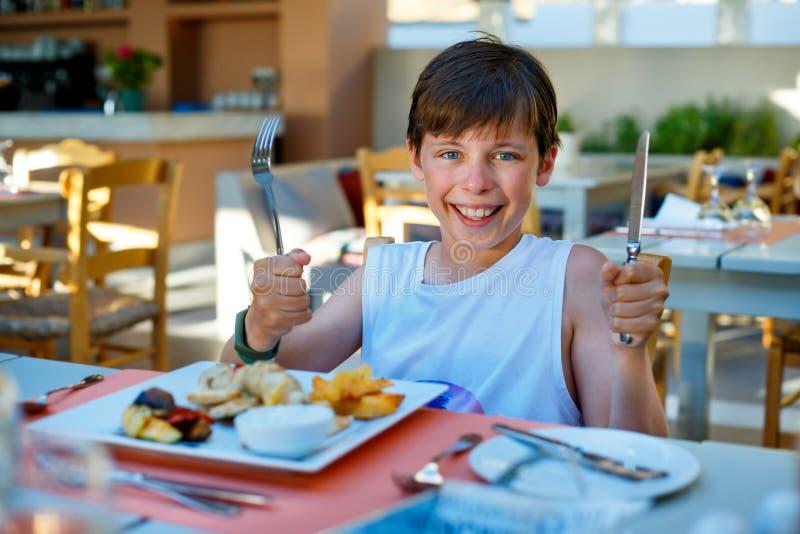 Den lyckliga gulliga pojken startar hans matställe Rymma en sked och en gaffel i handen royaltyfri fotografi