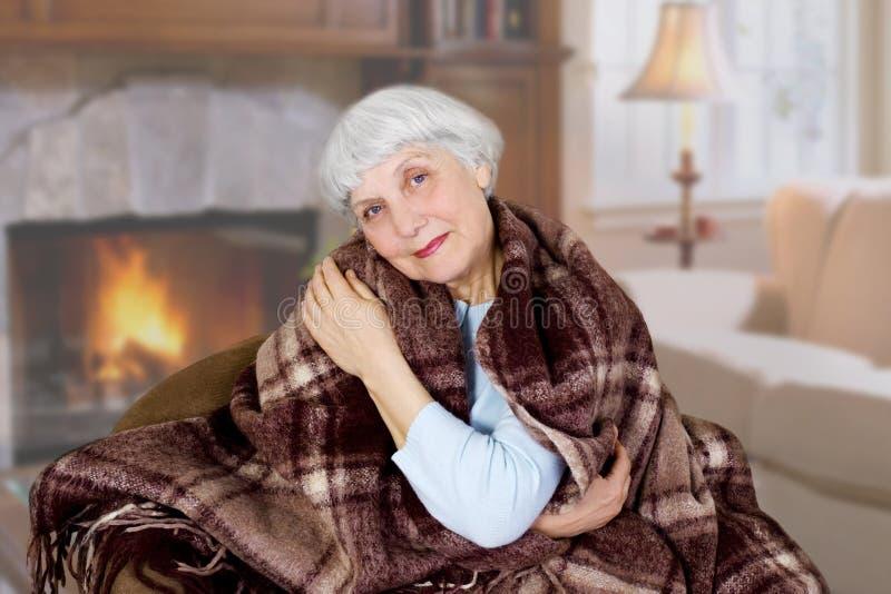 Den lyckliga härliga äldre kvinnan sitter dolt med en filt i rummet moder farmor royaltyfri foto