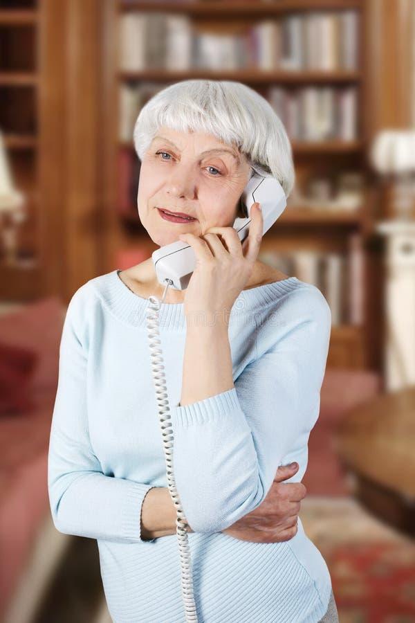 Den lyckliga härliga äldre kvinnan talar på telefonen, modern, farmor fotografering för bildbyråer