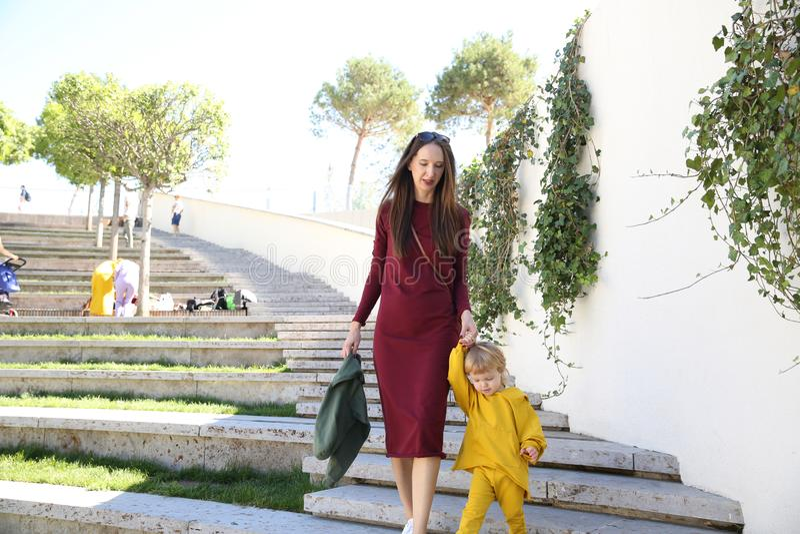 den lyckliga härliga kvinnan med ett småbarn i ljus kläder går i parkerar royaltyfri bild