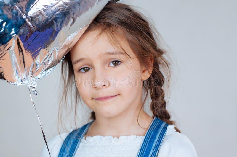 Den lyckliga härliga lilla flickan som rymmer en silver, stelnar ballongen i form av nummer F?delsedagber?m arkivfoto