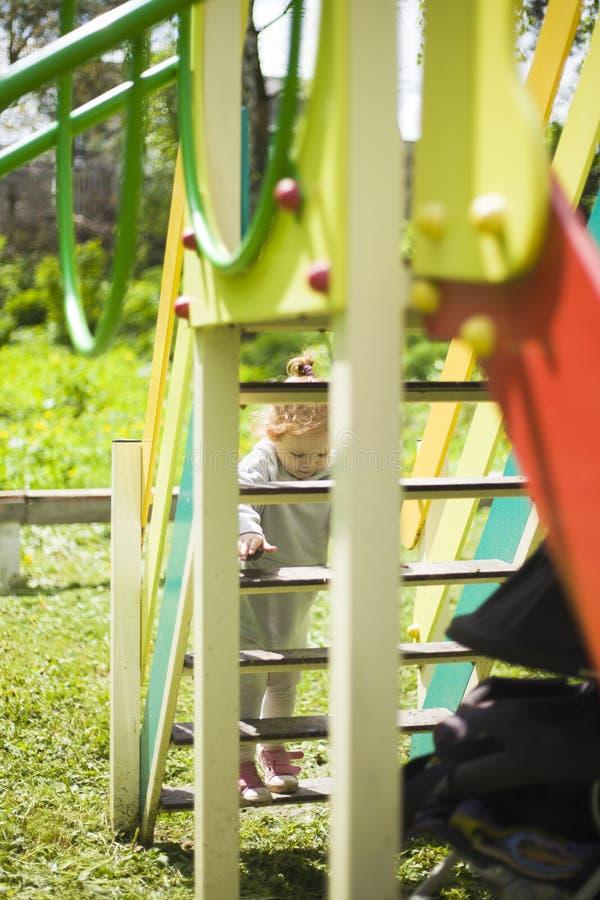 Den lyckliga härliga lilla rödhårig manflickan klättrar glidbanan på lekplatsen royaltyfri foto