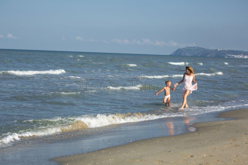 Den lyckliga härliga mamman och barnet har gyckel i vatten på havsstranden arkivbild