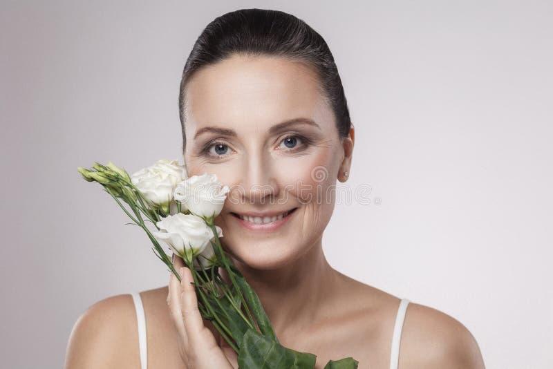 Den lyckliga härliga mogna kvinnan med perfekt hud och åldriga skrynklor är lutar på blommor med toothy leende Begrepp för hudoms arkivfoton