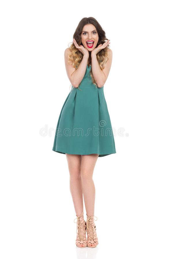 Den lyckliga härliga unga kvinnan i gröna Mini Dress And High Heels är det hållande huvudet, i händer och att ropa royaltyfria foton