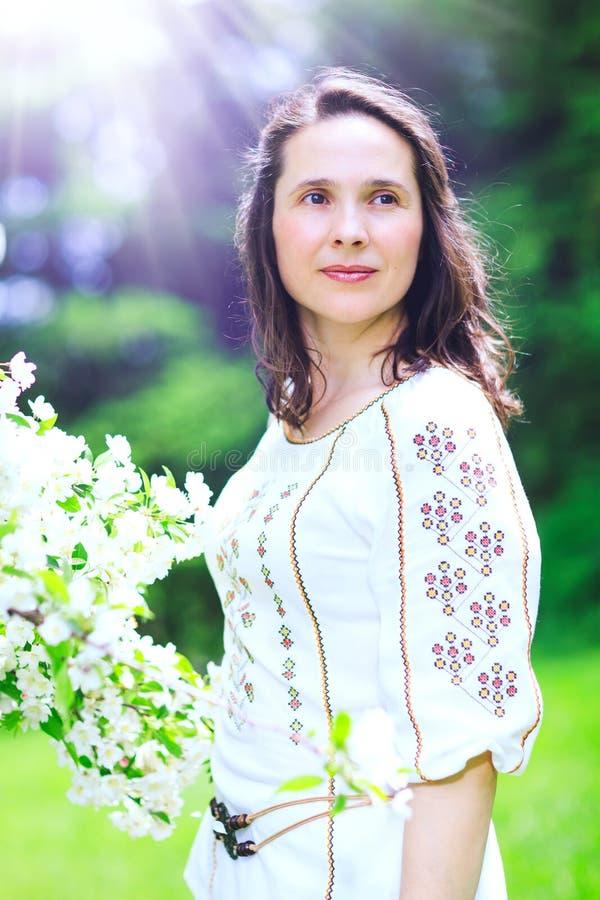 Den lyckliga härliga unga kvinnan med blusen dekorerade med romare royaltyfri foto