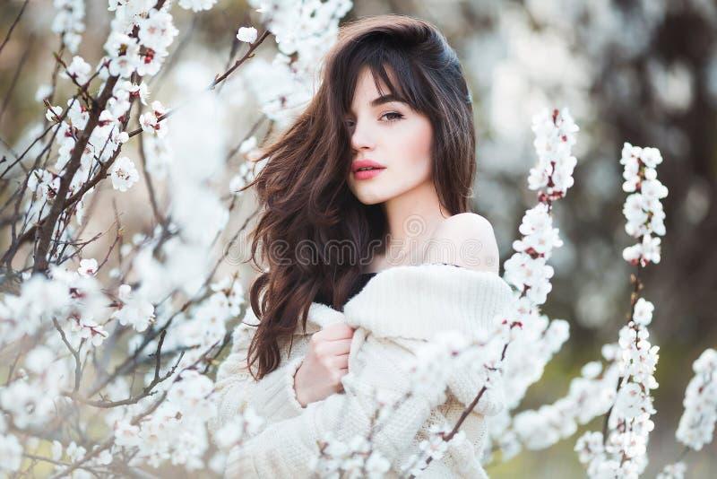 Den lyckliga härliga unga kvinnan med långt svart sunt hår tycker om nya blommor, och solljus i blomning parkerar royaltyfria bilder