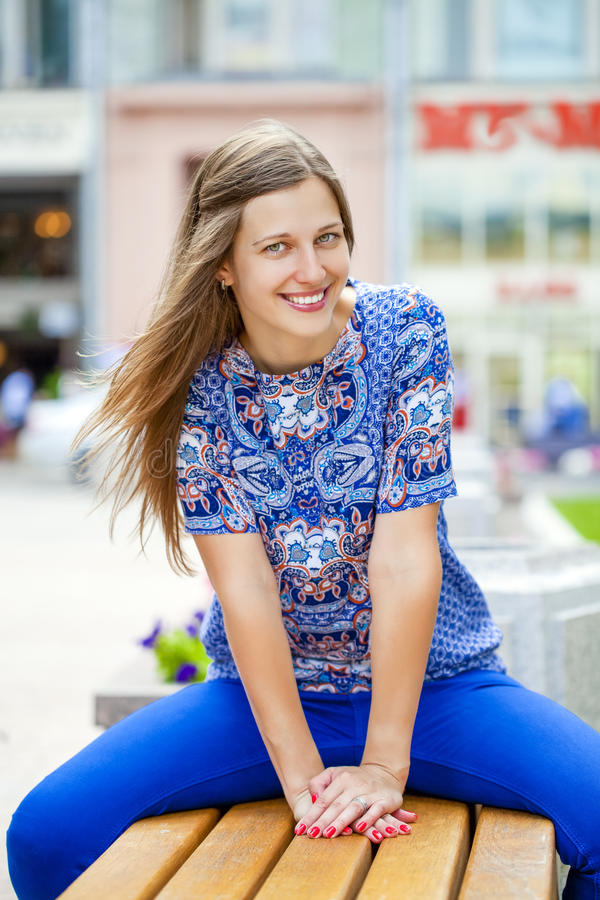 Den lyckliga härliga unga kvinnan sitter på en bänk arkivbilder