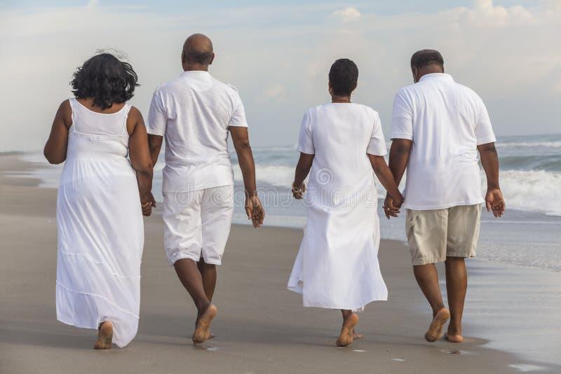 Den lyckliga höga afrikanska amerikanen kopplar ihop mankvinnor på stranden arkivfoto